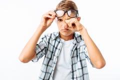 Il ragazzo teenager che il ribaltamento pulisce i suoi strappi della mano, frustrazione dopo la scuola, nello studio su un fondo  immagine stock