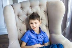 Il ragazzo teenager contrariato che si siede a casa Fotografia Stock