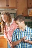 Il ragazzo teenager nasconde il messaggio sul suo telefono cellulare dalla madre curiosa Immagini Stock