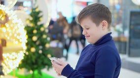 Il ragazzo teenager paffuto sta nel centro commerciale Cenni storici dell'albero di Natale Nelle mani di tenuta dello smartphone  stock footage
