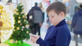 Il ragazzo teenager paffuto sta nel centro commerciale Cenni storici dell'albero di Natale Nelle mani di tenuta dello smartphone  archivi video