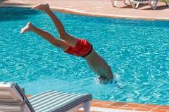 Il ragazzo teenager si tuffa e nuota nello stagno immagini stock