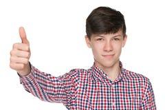 Il ragazzo teenager tiene il suo pollice su fotografia stock