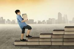 Il ragazzo tiene i libri e la passeggiata sulla scala dei libri Immagini Stock