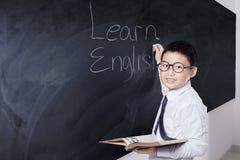 Il ragazzo tiene il libro e scrive impara l'inglese Fotografia Stock