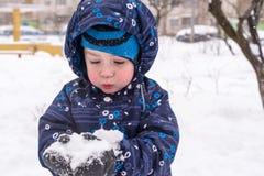 Il ragazzo tiene la neve in mani Fotografie Stock