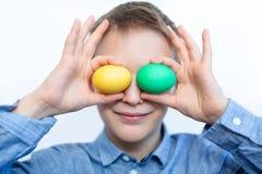Il ragazzo tiene le uova variopinte Uovo verde e giallo nelle mani del ragazzo Il ragazzo allegro tiene le uova vicino agli occhi fotografia stock
