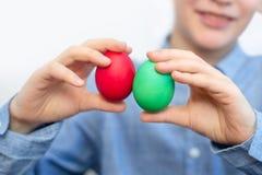 Il ragazzo tiene le uova variopinte Uovo verde e rosso nelle mani del ragazzo fotografie stock