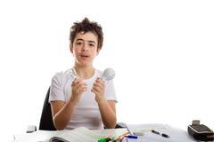 Il ragazzo tiene una lampadina e un prototipo della stampa 3D mentre fa il homew Fotografia Stock Libera da Diritti