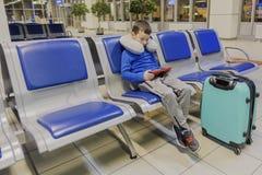 Il ragazzo in un aeroporto vuoto uno aspetta l'aereo ed i giochi in suo aggeggio favorito Fotografia Stock