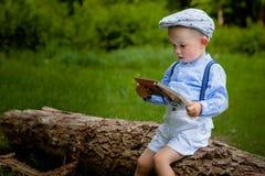 Il ragazzo un poco di due anni che si siede su un albero e legge un libro hildren il giorno Fotografia Stock Libera da Diritti