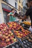 Il ragazzo vende le pesche e l'altra frutta sul mercato dell'aria aperta di briancon nell'Alta Provenza francese Immagine Stock Libera da Diritti