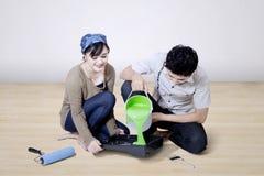 Il ragazzo versa la pittura verde a casa Immagini Stock Libere da Diritti