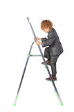 Il ragazzo in vestito aumenta sullo step-ladder Fotografia Stock
