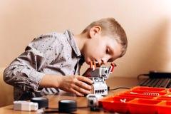 Il ragazzo vestito in camicia grigia fa un robot dal costruttore robot allo scrittorio nella scuola di robotica fotografia stock libera da diritti