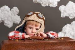 Il ragazzo vestito come pilota dell'aeroplano si siede fra le nuvole con la vecchia valigia ed i sogni fotografia stock libera da diritti