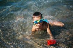 Il ragazzo in vetri di nuoto gioca sul Mar Nero in Crimea Fotografia Stock