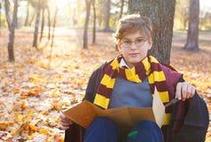 Il ragazzo in vetri sta nel parco di autunno con le foglie dell'oro, tiene il libro in sue mani, dura in abito nero immagini stock libere da diritti