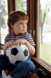 Il ragazzo vuole giocare il calcio un giorno piovoso Immagine Stock