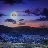 Il raggio luminoso cade sul pendio di collina con il villaggio di autunno in montagna a fotografie stock libere da diritti