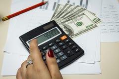 Il ragioniere conta i soldi con un calcolatore Fotografie Stock Libere da Diritti