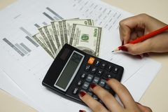 Il ragioniere conta i soldi con un calcolatore Fotografia Stock