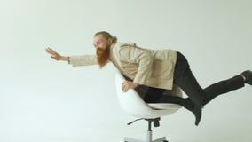 Il rallentatore dell'uomo d'affari divertente barbuto si diverte la guida sulla sedia dell'ufficio su fondo bianco