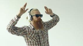 Il rallentatore di giovane uomo barbuto felice in occhiali da sole e le cuffie che ballano ed ascoltano musica su fondo bianco video d archivio