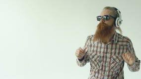 Il rallentatore di giovane uomo barbuto felice in occhiali da sole e le cuffie che ballano ed ascoltano musica su fondo bianco archivi video