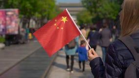 Il rallentatore di un bloger della giovane donna che tiene una piccola bandiera cinese cammina il centro commerciale di Quinmen M stock footage