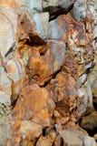 Il rame e la ruggine astratti hanno colorato le rocce sul bluff Fotografia Stock