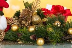 Il ramo del pino ha abbellito le palle di Natale, la statuetta del ricordo e la scatola dorate con il regalo su giallo Fotografia Stock