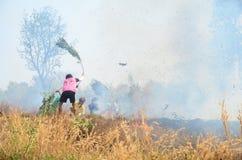 Il ramo e la foglia di uso della gente tailandese estinguono il fumo e le fiamme Immagini Stock Libere da Diritti
