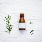 Il ramo fresco dei rosmarini con l'olio essenziale della bottiglia ha installato sul whi Fotografia Stock