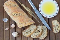 Il ramoscello del coltello di pane, dell'olio vegetale, dell'aglio e dell'orzo Fotografie Stock