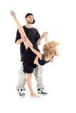 Il rapper tiene le mani della ragazza della ginnasta, che sta su una gamba immagine stock