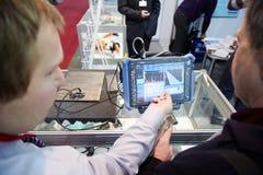 Il rappresentante della società spiega l'operazione di defectoscope modulare portatile Fotografia Stock