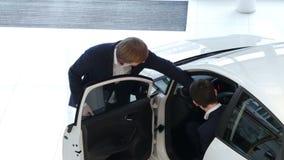 Il rappresentante spiega alle specifiche dell'automobile del cliente stock footage