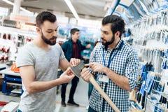 Il rappresentante sta mostrando a cliente barbuto la nuova ascia nel deposito delle macchine utensili immagine stock libera da diritti