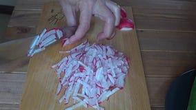 Il ravanello delle fette del cuoco su un tagliere, si chiude sui ravanelli di taglio video d archivio