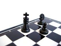 Il re nero di scacchi si leva in piedi con la figura su una scheda di scacchi Fotografia Stock