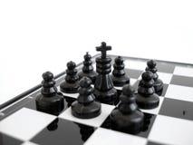 Il re nero di scacchi si leva in piedi su una scheda di scacchi con le figure Fotografie Stock Libere da Diritti