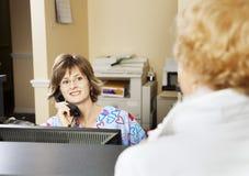 Il receptionist accoglie il paziente fotografie stock