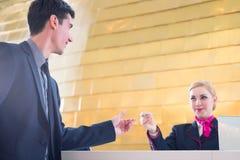 Il receptionist dell'hotel controlla l'uomo che dà la carta chiave Immagine Stock