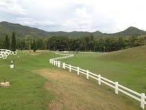 Il recinto attraversa la montagna verde Fotografia Stock Libera da Diritti