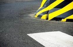 Il recinto del blocco in calcestruzzo della costruzione ha barrato il modello nero giallo di cautela su un bordo della strada, de immagine stock libera da diritti