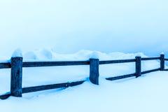 Il recinto o la barriera ed i mucchi di neve nella campagna o nel villaggio nel giorno di inverno freddo immagine stock