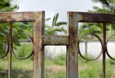 Il recinto verde del metallo è arrugginito con gli anni di negligenza Immagini Stock