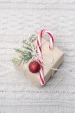 Il regalo di Natale con il bastoncino di zucchero su bianco ha tricottato il fondo Immagine Stock