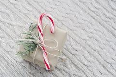 Il regalo di Natale con il bastoncino di zucchero su bianco ha tricottato il fondo Fotografia Stock Libera da Diritti